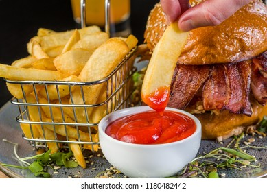 Dipping a french fry chip into a bowl of tomato sauce with a basket of chips and hamburger in the background