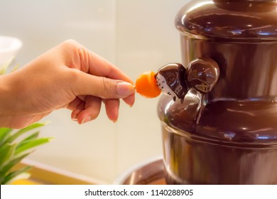 Dipping fresh fruit into a chocolate fondue fountain with a skewer