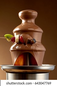 Dipping fresh fruit into a chocolate fondue fountain with a skewer of summer fruits dripping sauce in the foreground