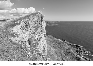 Dipping Portland Limestone capping Gad Cliff on Dorset's Jurassic Coast in England. A monochrome edit.