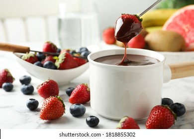 Dipping strawberry into fondue pot with chocolate on white marble table