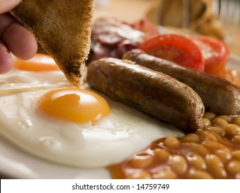 Dipping Toast into a Fried Egg on a Full English Breakfast