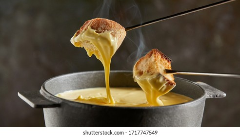 Dipping toasted bread into a hot cheese fondue dripping from the forks in a close up view on a dark background with steam