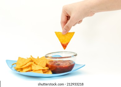 Dipping tortilla chips with salsa sauce in dish on isolated white background