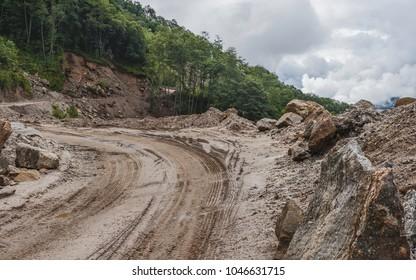Dirang, Arunachal Pradesh, India. Muddy main highway (H229) between Bomdila and Tawang and forested slopes and thick cloud near Bomdila, Arunachal Pradesh, India.