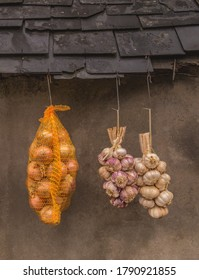 Direct marketing of garlic braid and onions hanging in front of old facade