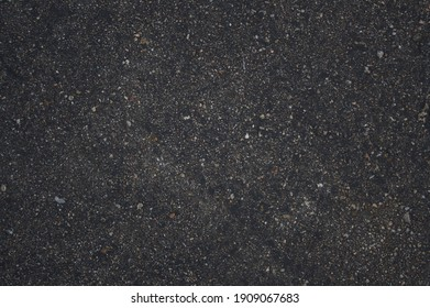 Direct overhead shot the rough texture of dark asphalt full of shiny stones that resemble a starry sky.