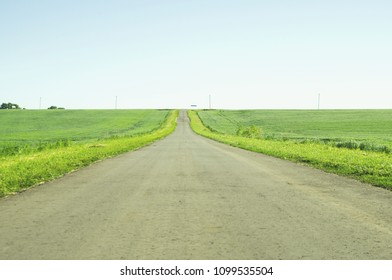 Direct road between fields stretching beyond the horizon