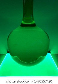 Direct view of green colour capsule glass vase with long neck illuminated uplight glow and create ripple of the water inside against the wall dyed with colour light background.