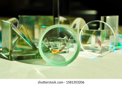 Direct view through circular concave convex lens and triangular glass prism. Refraction of light captures overall image of sparkling glass and dichroic cube prisms inside centre concave lens