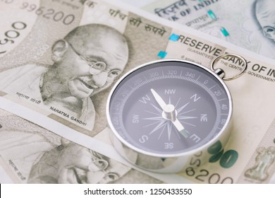 Direction of india financial and economy, new asia developing and emerging market high growth country concept, closed up of compass on indian rupee banknotes on table.