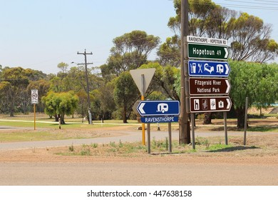 Direction road signs to Ravensthorpe, Hopetoun, caravan camping site, gas station, restaurant and Fitzgerald National Park at crossroads in Western Australia