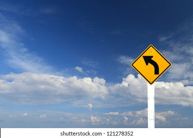 Direction sign- left turn warning on blue sky background with blank for text