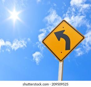 Direction sign- left turn warning on blue sky background
