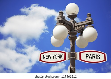 Direction sign and street lamp. Paris and New York