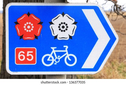 Direction sign for trans England cycle route showing the red and white roses of Lancashire and Yorkshire