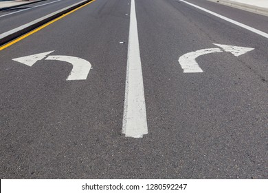 Directional arrows pointing left and right painted on a highway.