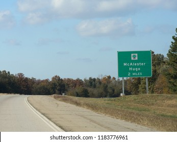 Directional sign by the roadside two miles away from McAlester Hugo in Oklahoma.