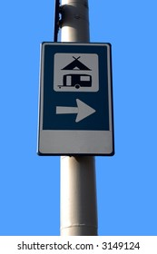 directional sign for camping site against a clear blue sky