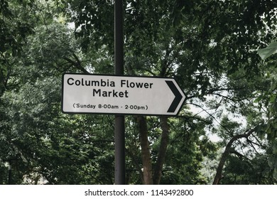 Directional sign to Columbia Flower Market in London, UK, against green trees, includes opening hours.