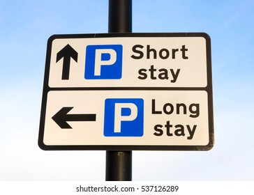 Directional sign for a long stay and short stay carpark against a partly cloudy sky background