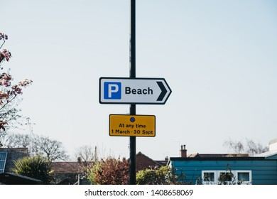 Directional sign to the parking by the beach and restriction dates on a lap post in Norfolk, England, UK.