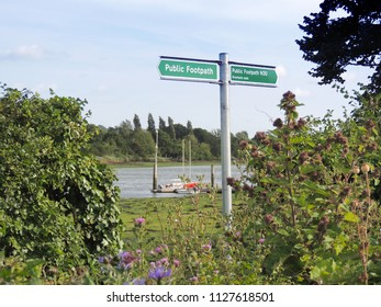 """Directional sign post by the river that says, """"Footpath"""" in both directions."""