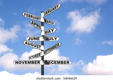 A directional signpost showing the months of the year against a blue cloudy sky.