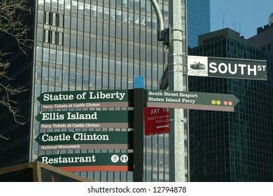 Directional signposts in New York City displaying direction to local tourist attractions such as Statue of liberty & Ellis Island