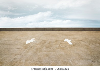 Directional traffic arrows on a concrete parking garage rooftop with a cloudy sky.