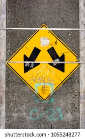 A directional traffic sign on a concrete pillar with two arrows directs motorists around the obstacle.