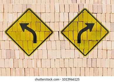 Directional traffic signs in opposite positions stamped on pile of bricks, like a graffiti