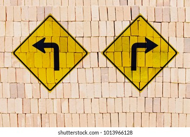 Directional traffic signs in opposite positions stamped on pile of bricks,