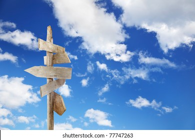 Directional unfinished wood signs over a blue sky