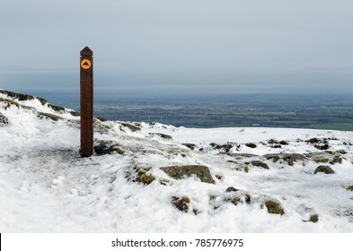 Directional way marker post on Brown Clee Hill, the highest peak in Shropshire, England, UK. Winter landscape under snow.