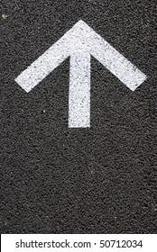 directional white arrow sign on the asphalt road