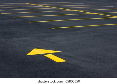Directional yellow arrow symbol in a typical parking field