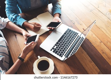 Directly above of hipster lifestyle and creative workspace in cafe - Business women teamwork with laptop, mobile phone in coffee shop. startup online marketing, top view - vintage effect filter.