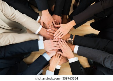 Directly above shot of business team stacking hands in office