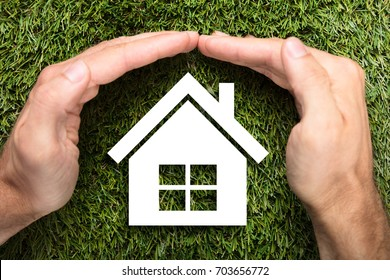 Directly above shot of businessman's hands covering paper house on grass