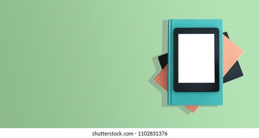 directly above shot of e-book reader, e-reader on stack of books on green desktop