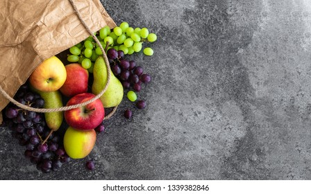directly above shot of fresh organic local fruits in brown paper bag on stone background