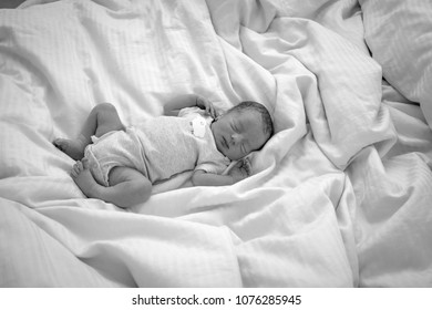 Directly above shot of newborn baby boy sleeping on bed
