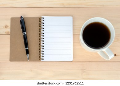 Directly above shot of notepad and cup of coffee