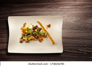 Directly above shot of a stylish nouvelle cuisine plate of beetroot and walnut salad on wooden background