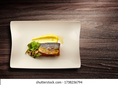 Directly above shot of a stylish Nouvelle Cuisine plate of fish on salad on wooden background