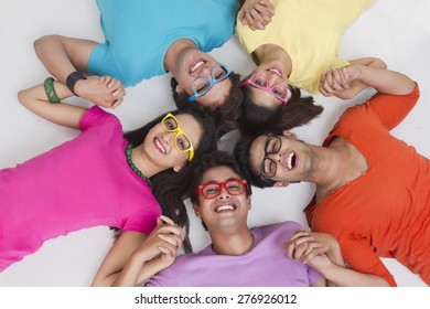 Directly above shot of trendy friends holding hands while lying in circle on white background