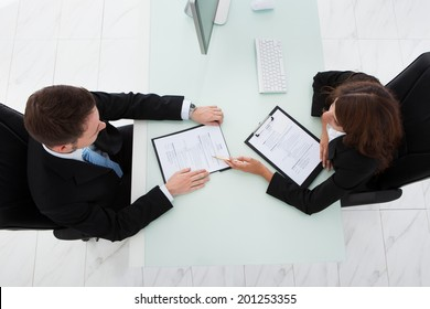 Directly above shot of young businesswoman interviewing male candidate in office