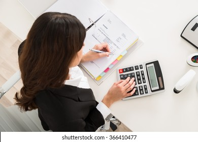 Directly above shot of young businesswoman doing financial calculation at desk in office