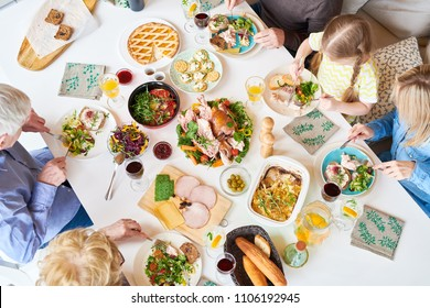 Directly above view of big happy family sitting at dinner table enjoying delicious homemade food during celebration